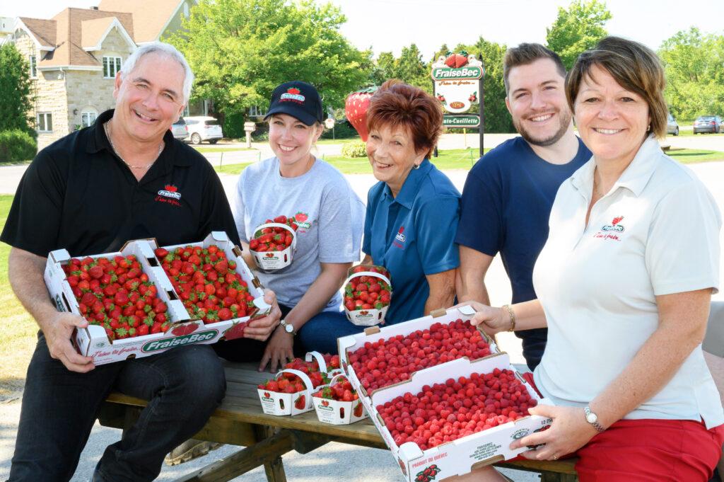 Famille FraiseBec, plusieurs personnes tiennent des paniers de fraises